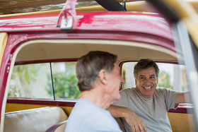 smiling senior men in vintage car